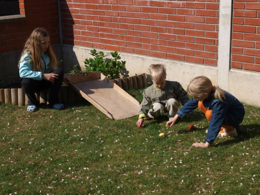 Otroci se zabavajo ob kotaljenju pirhov.